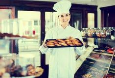 Frauenbäcker, der warme geschmackvolle Hörnchen zeigt Stockbilder