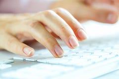 FrauenBüroangestellter, der auf der Tastatur schreibt Stockfotografie
