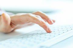 FrauenBüroangestellter, der auf der Tastatur schreibt Stockbild