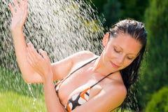 Frauenbadeanzug-Spritzenwasser des Sommergartens lächelndes lizenzfreie stockbilder