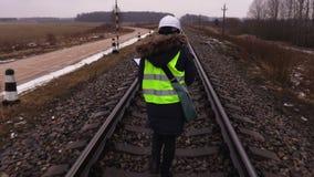 Frauenbahnangestellter, der Schienen kontrolliert stock video footage