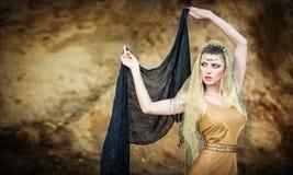 FrauenBauchtänzerin mit Schleier gegen Felsenstrand Stockfoto