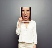 Frauenbedeckungsbild mit großem verärgertem Gesicht Stockbild