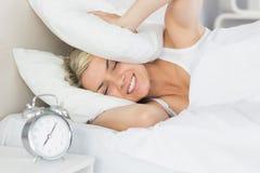 Frauenbedeckungsohren mit Kissen und Wecker im Vordergrund Stockfoto