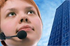 Frauenbediener mit headphoneson Gebäuden des blauen Himmels und des Geschäfts Lizenzfreie Stockfotografie