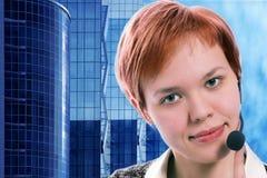 Frauenbediener mit headphoneson Gebäuden des blauen Himmels und des Geschäfts Stockbild