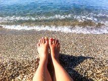 Frauenbeine auf dem Strand lizenzfreies stockbild