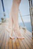 Frauenbeine auf der Yachtplattform Stockfoto