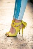Frauenbeine in den ledernen gelben Sandalen des hohen Absatzes im Freien in der Stadt stockbild