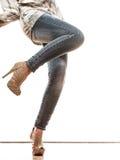 Frauenbeine in den Schuhen der Denimhosen-hohen Absätze Lizenzfreies Stockbild