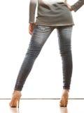Frauenbeine in den Schuhen der Denimhosen-hohen Absätze Stockfoto