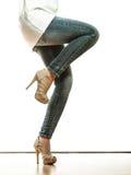 Frauenbeine in den Schuhen der Denimhosen-hohen Absätze Stockfotos