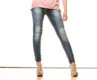 Frauenbeine in den Schuhen der Denimhosen-hohen Absätze Stockbild