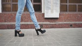 Frauenbeine in den schwarzen Plattformschuhen und -Blue Jeans, die in die Stadtstraße gehen stock footage