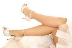 Frauenbeine in der Hochzeitskleiderlage Stockfotos