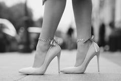Frauenbeine, die hohe Absätze tragen Stockfotografie