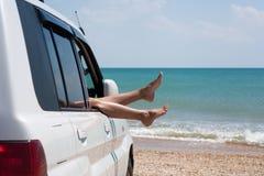 Frauenbeine im Autofenster Stockfoto