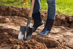 Frauenbeine Landwirt In Rubber Boots mit Schaufel im Garten Lizenzfreie Stockfotos