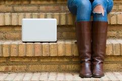 Frauenbeine mit einem weißen Computer folgend stockbild
