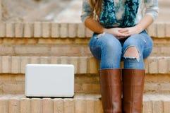 Frauenbeine mit einem weißen Computer folgend lizenzfreies stockfoto