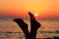 Frauenbeine und -abend setzen auf dem Sonnenuntergang auf den Strand Lizenzfreies Stockbild