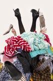 Frauenbeine und -hände, die heraus von einem großen Stapel von Kleidung und von Zubehör erreichen Lizenzfreie Stockfotos