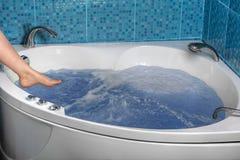 Frauenbeine wird in den Badekurort der heißen Wanne gesenkt Lizenzfreie Stockbilder
