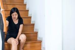 Frauenbeinschmerz mit ihr Knie zu Hause berühren und herauf Treppe gehen lizenzfreie stockbilder