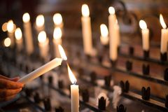 Frauenbeleuchtung-Gebetkerze Stockfoto