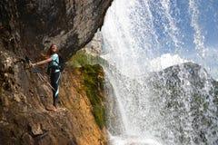 Frauenbergsteiger auf Klippe durch Wasserfall stockfotografie