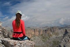 Frauenbergsteiger, der auf Bergspitze sitzt lizenzfreie stockbilder