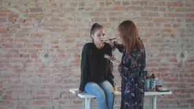 Frauenberufsmaskenbildner macht Wachs Plastikmake-up für Kunstkino und malt Gesicht des jungen Mädchens und schafft Bild stock footage