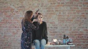 Frauenberufsmaskenbildner macht Wachs Plastikmake-up für Kunstkino und malt Gesicht des jungen Mädchens und schafft Bild stock video footage