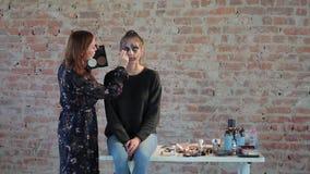 Frauenberufsmaskenbildner macht Wachs Plastikmake-up für Kunstkino und malt Gesicht des jungen Mädchens und schafft Bild stock video