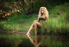 Frauenbikini, der auf der Seeseite sitzt Stockfoto