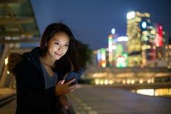 Frauenblick auf Telefon Stockfotografie