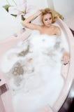 Frauenblondine in einem Bad mit Schaumgummi stockfoto