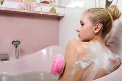Frauenblondine in einem Bad mit Schaumgummi stockfotografie