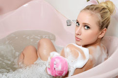 Frauenblondine in einem Bad mit Schaumgummi stockfotos