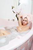 Frauenblondine in einem Bad mit Schaumgummi lizenzfreies stockfoto