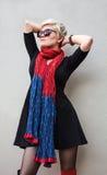 Frauenblondine im schwarzen Kleidchen, roter Schal, Sonnenbrille Art- und Weisebaumuster-Schuß Stockfotos