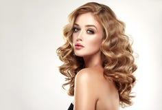 Frauenblondine mit umfangreicher, glänzender, gelockter und loser Frisur stockfotografie