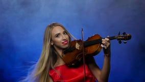 Frauenblondine spielt die Geige Rauchiger Hintergrund Langsame Bewegung stock footage
