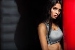 Frauenboxer nahe rotem Sandsack Stockfotografie