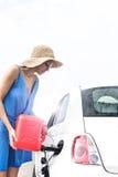 Frauenbrennstoffaufnahmeauto gegen klaren Himmel am sonnigen Tag Stockfoto