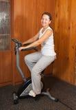 Frauenübung auf spinnendem Fahrrad Stockbild