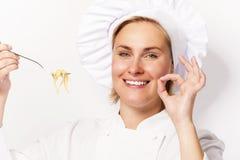 Frauenchef, der ein Zeichen perfekt, mit Teigwarennudel auf Gabel, ov zeigt Stockfotos