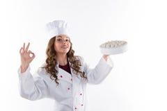 Frauenchef, der einen Kuchen hält stockbild