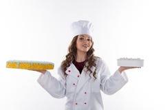 Frauenchef, der einen Kuchen hält stockbilder