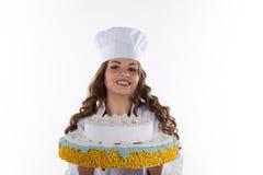 Frauenchef, der einen Kuchen hält lizenzfreies stockbild